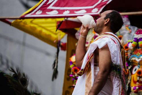 A Krishna worshipper blowing the conch shell to start Ratha Yatra