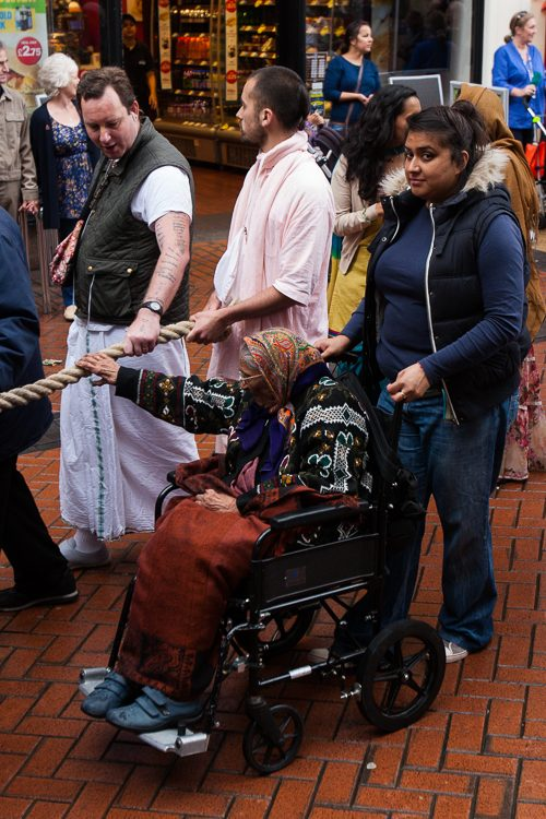 Old lady in a wheelchair touching the ropes that pull the chariot for luck
