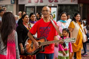 A guitar player joins the Ratha Yatra procession