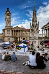 People eating street food on the steps of Chamberlain Square