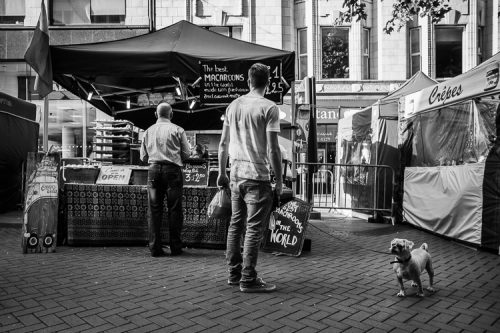 Young man with a cute dog outside the macaroons stall