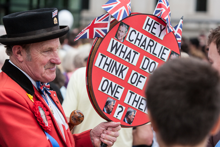 A guy with a sign challenging Prince Charles to comment on the new library