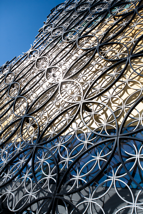 Sun glinting on the jewel-like tapestry of the library circular metalwork