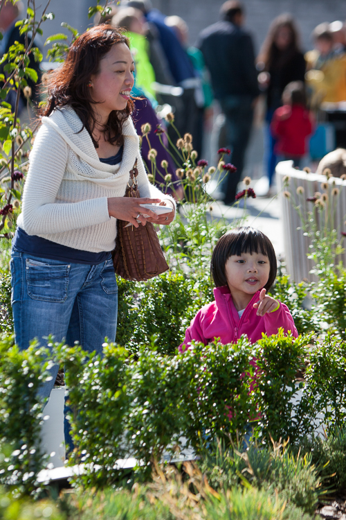 A young girl pointing at some plants in a raised container on the Discovery Terrace