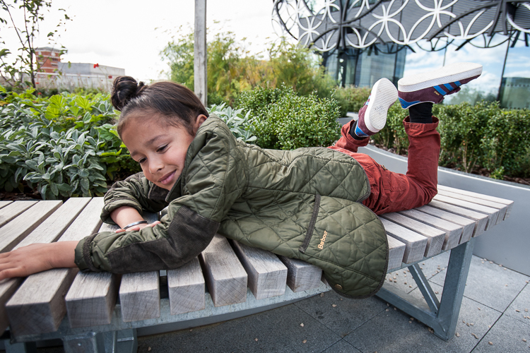 Young girl lying on the Discovery Terrace bench