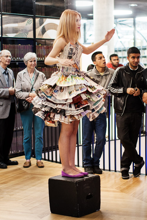 Teen model in a paper dress posing on a black box