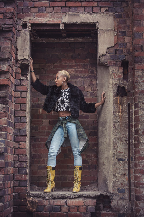 Model posing in a exposed brick niche