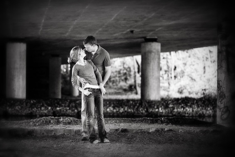 A couple  photographed under the bridge on a rainy day