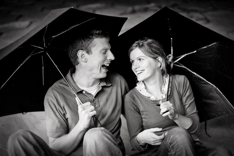 Engagement session photo - a laughing couple holding umbrellas