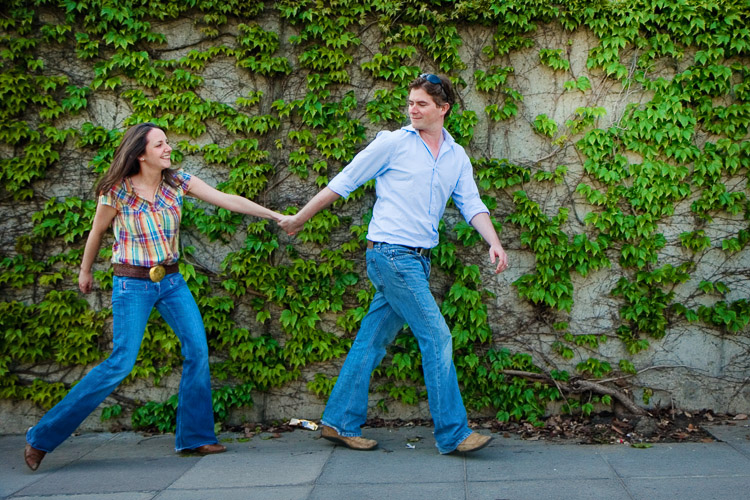 A couple waling along the ivy-grow concrete wall