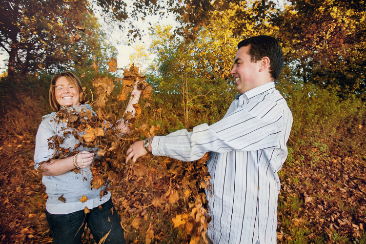 Engagement session = a couple in the park throwing autumn leaves at each other