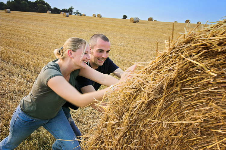 Engagement session photo - a couple pushing a straw bale