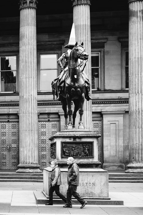 An equestrian statue of the Duke Wellington capped with a traffic cone