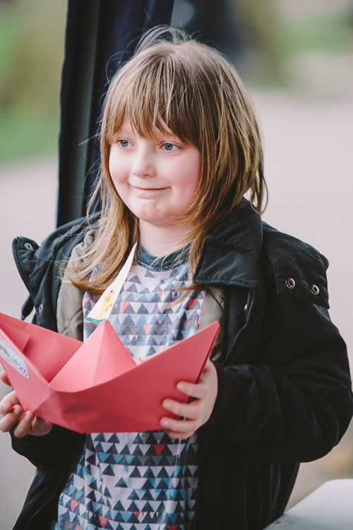 Little girl proudly holding her paper boat