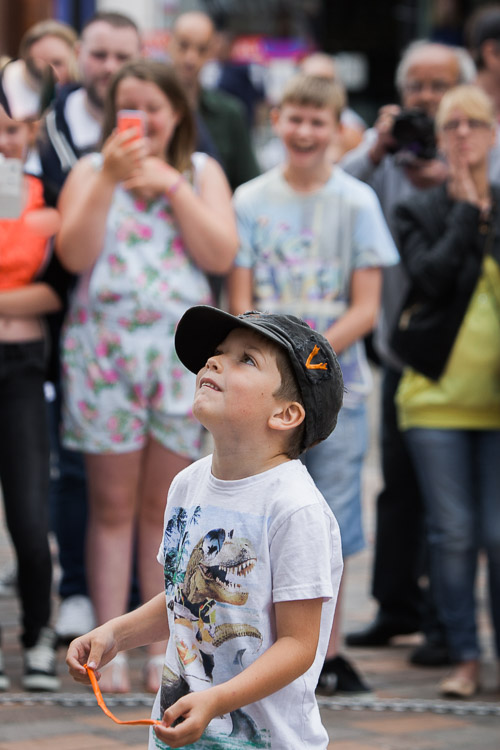 A young member of the audience is recruited to help in a street performance