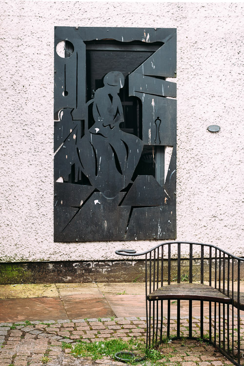 Cutout piece depicting a seated woman in thought