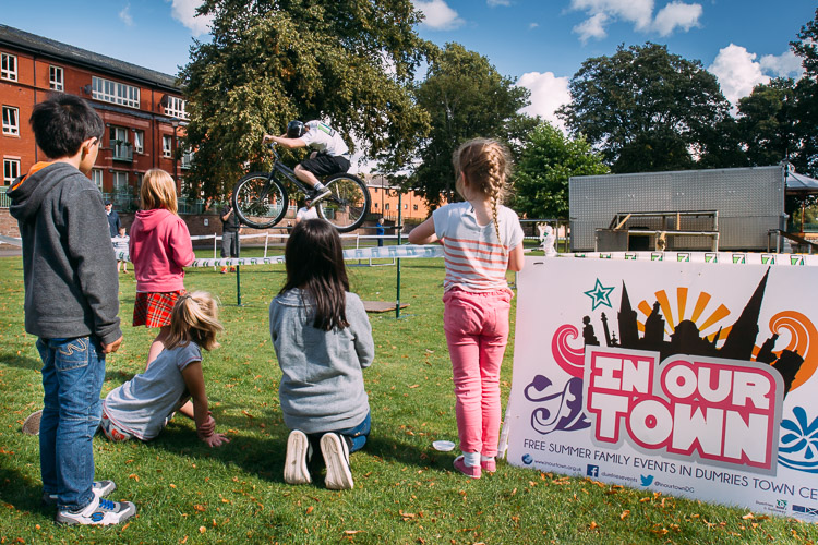 Children watching a 7Stanes rider jumpring over the high bar at Dock Park Dumfries