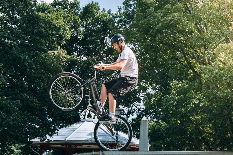 A member of 7Stanes bike display team performs a stunt on the top of the trailer