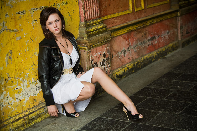 A model sitting against a weathered wall