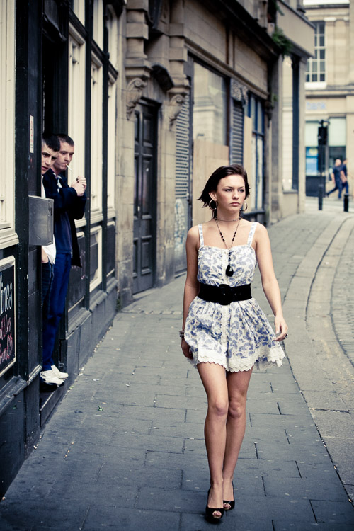 Two pub goers looking at a girl passing on the street