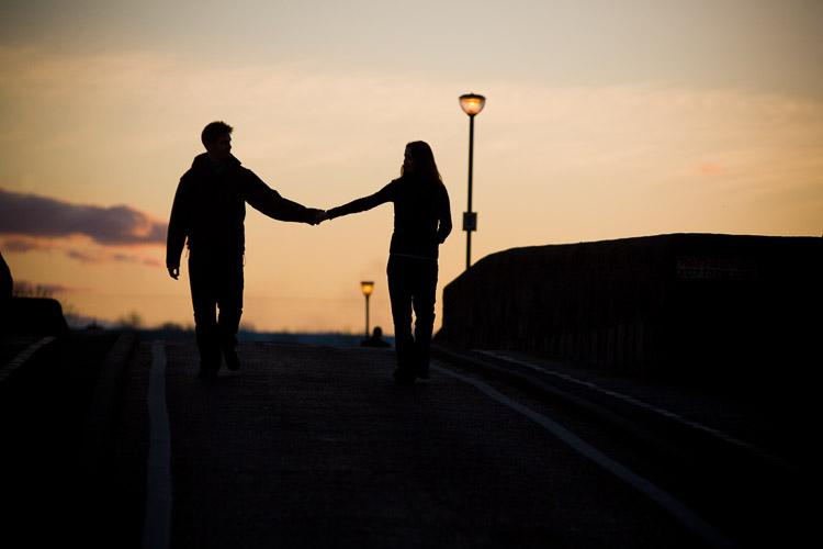 A couple walking on the bridge at sunset