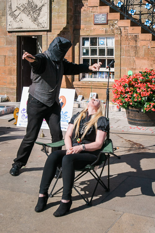 Blindfolded performer cuts the rose with a sharp open razor