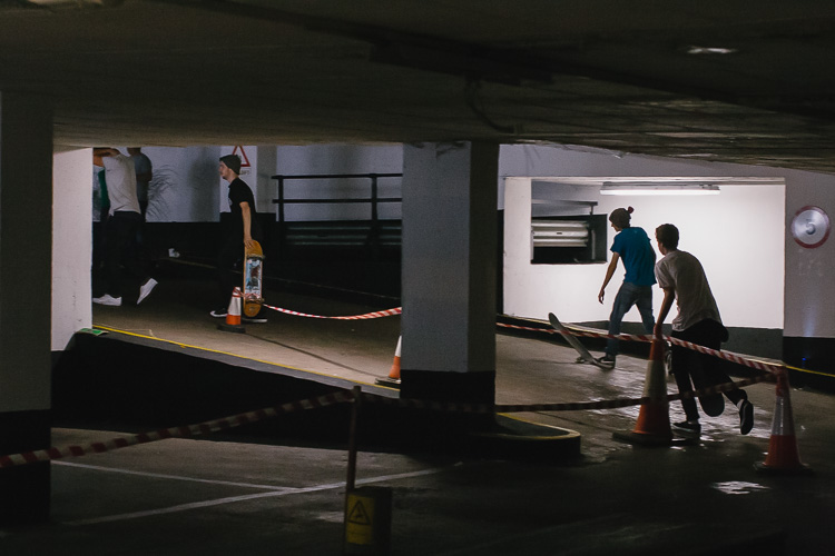 Skateboarders in between the car park levels