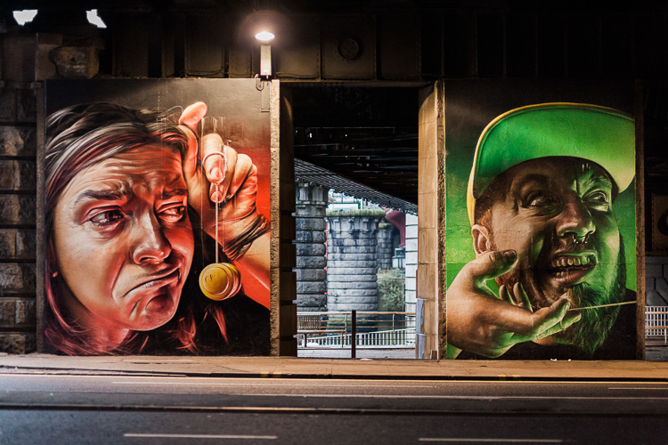 The two colourful panels on the left of 'The Five Faces' street artwork
