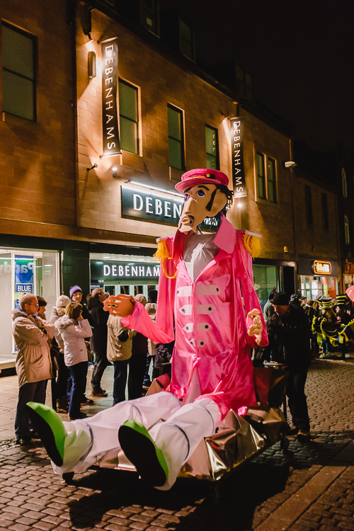 Dumfries Community Choir is followed by a giant Sergeant Pepper-esque character