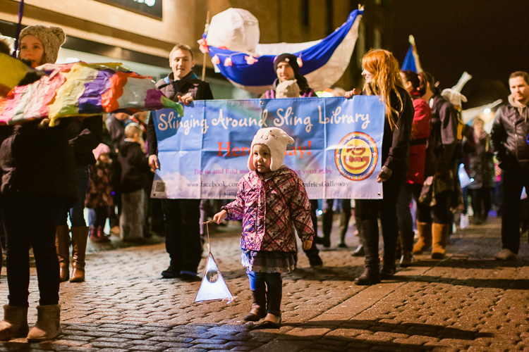 A little girl with a lantern leading the Sling library parade participants