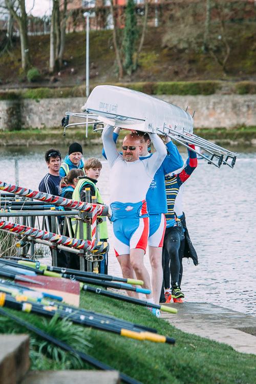 Rowing crew carrying the shell after the race
