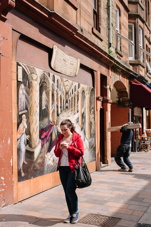 "A girl passing the mural named ""I Mak Siccar - Towards Scottish Independence"" by Jo McSkimming"