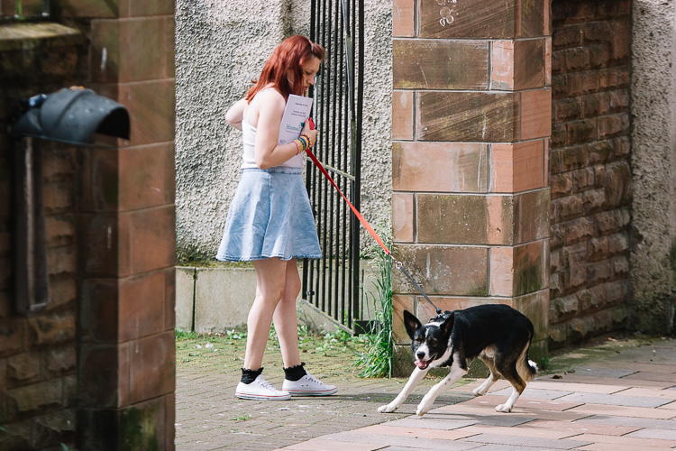 A young girl holding a housing application and a leash with a dog