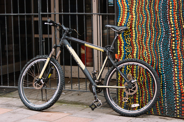 Bicycle parked outside a street art mural