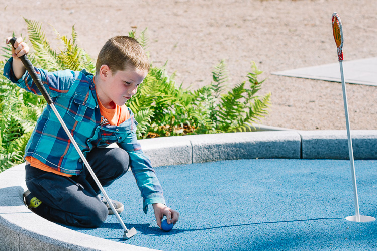 A boy preparing to putt at Peter Pan themed mini golf set at Dock Park