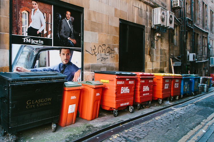Large advertising board at the back alley next to the row of rubbish bins in Glasgow