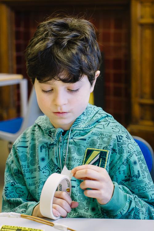 Boy pulling masking tape