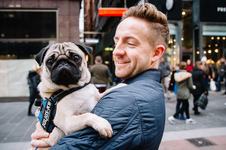 Street photography in Glasgow - a man carrying a pug