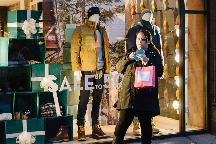 Xmas shopping break - a girl with a shopping bag stops to lights a sigarette