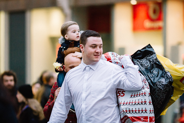 A young Glaswegian carrying his Xmas shopping Santa style
