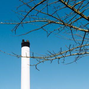 White chimney against the blue spring sky