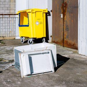 Yellow sandbox and broken white fridge