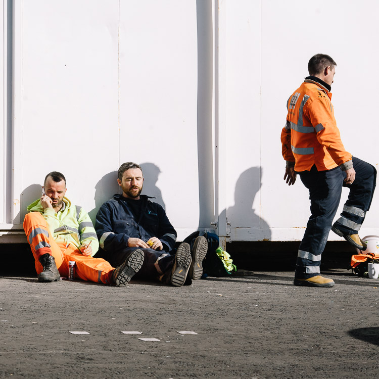 Urban photo - resting workmen in orange vests at lunch time
