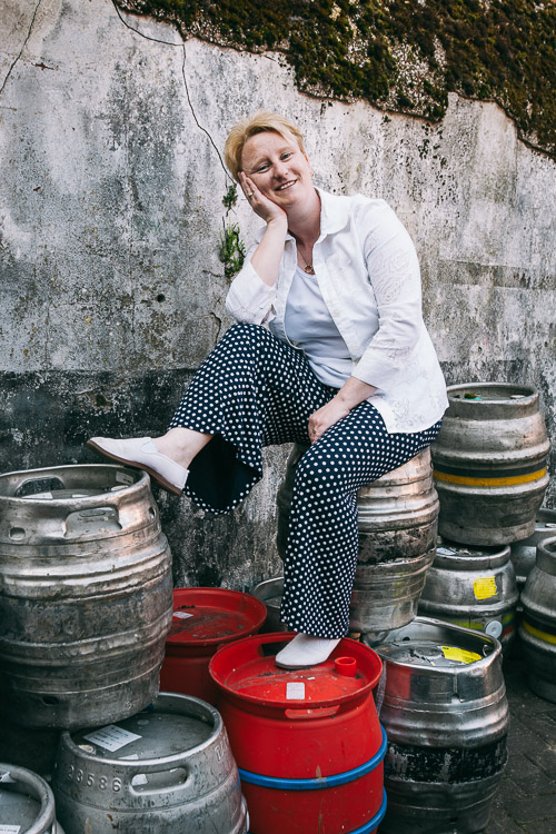 A backstreet urban portrait of a woman sitting on a pile of empty beer casks