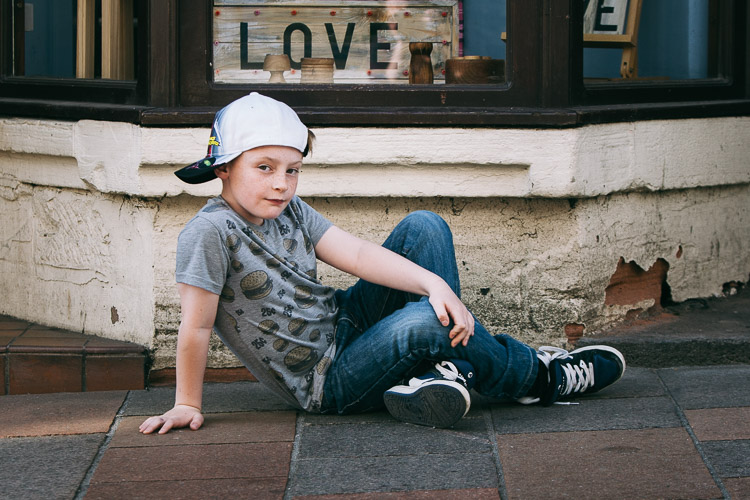 Urban portrait of a child that uses a shop window sign as a background