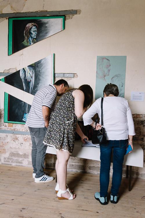Visitors perusing Alex's work