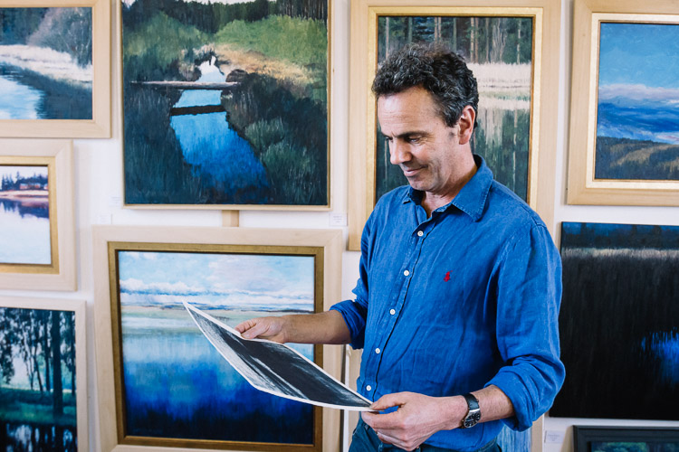 William examining his print in front of his finished paintings