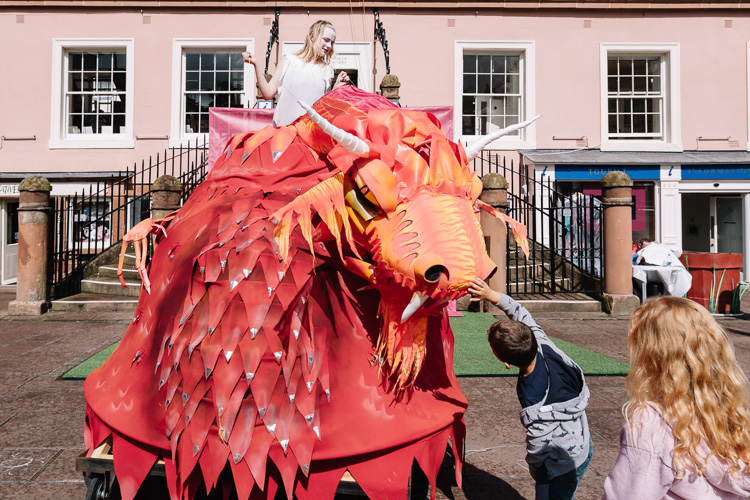 Kids touch the dragon who delivered the princess after the theatre act