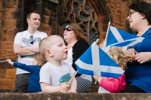 Spectators with Saltire flags at the annual Guid Nichburris festival float parade