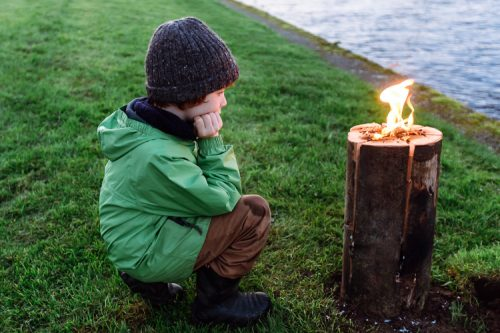 Boy looking at Nordic log fire